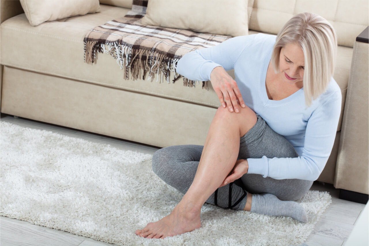 The woman checks her veins in the leg.