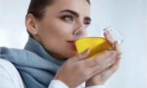 The woman drinks herbal medicine.