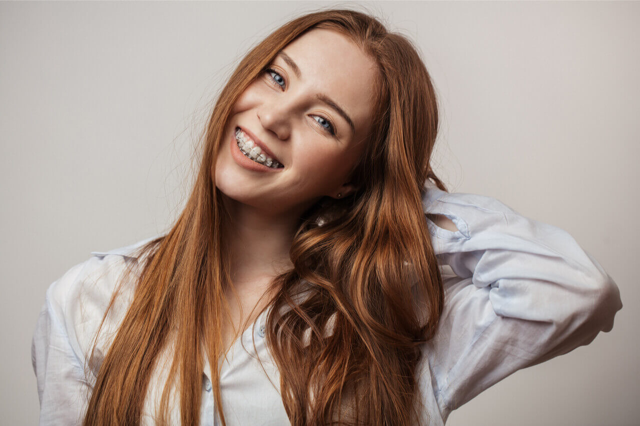 The woman has dental braces to correct the alignment of her teeth.
