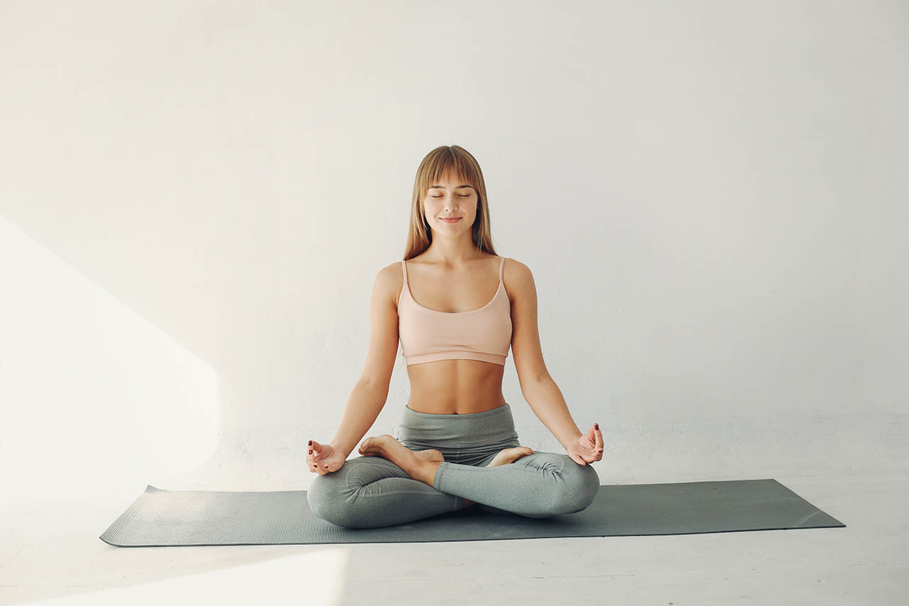 The woman is concentrating on her yoga practice.